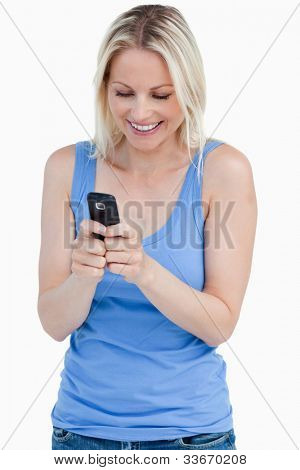 Smiling blonde woman sending a text with her cellphone against a white background