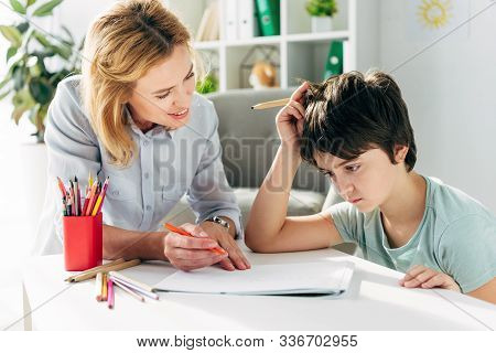 Kid With Dyslexia And Smiling Child Psychologist Sitting At Table And Holding Pencils