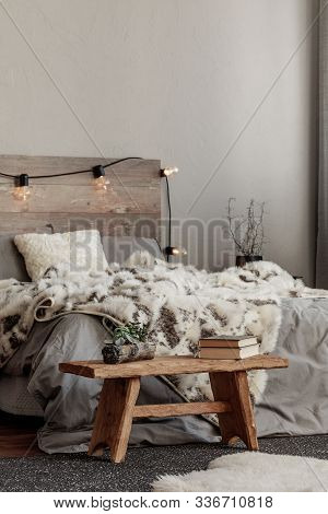 Warm Bedroom Interior With King Size Bed With Wooden Headboard With Light, Fury Blanket And Black Ni