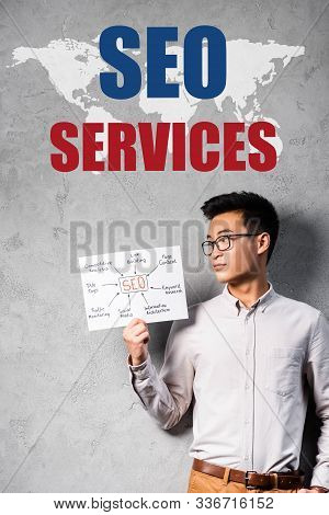 Asian Seo Manager Holding Paper With Concept Words Of Seo And Standing Near Seo Services Illustratio