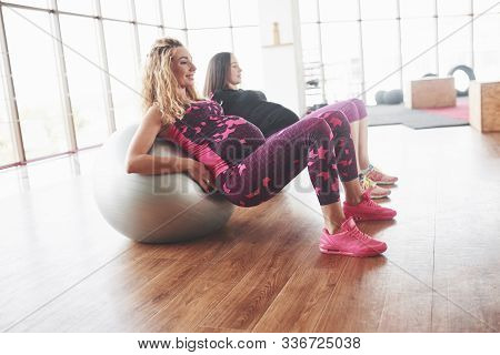 Side Photo Of Two Pregnant Women Doing Fitness Exersices Using Stability Balls.