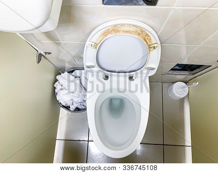Dirty Unhygienic Seat Of A Toilet Bowl With Limescale Stain At Public Restroom Close Up