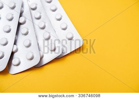 A Blister Pack Of Statins, Pills Tablets For Lowering Cholesterol On Yellow Background, Prevention A