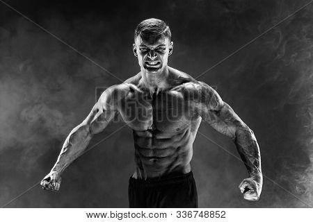 Very Brawny Guy Bodybuilder Posing. Beautiful Sporty Guy Male Power. Fitness Muscled Man. Roar. Smok