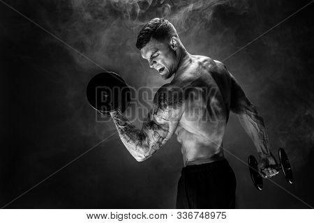Very Brawny Guy Bodybuilder. Portrait Of Roaring Muscular Man Lifting Dumbbell In Smoke. Studio Shot