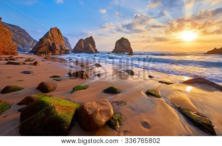 Ursa Beach in Portugal. Atlantic coast of Atlantic Ocean. Sunset and rocks sun waves and foam at sand of coastline picturesque landscape panorama.