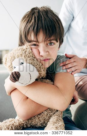 Kid With Dyslexia Holding Teddy Bear And Child Psychologist Hugging Him