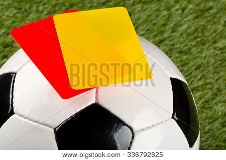 Close Up Of Referee Yellow And Red Cards On Top Of Soccer Ball Over Grass Background - Penalty, Foul