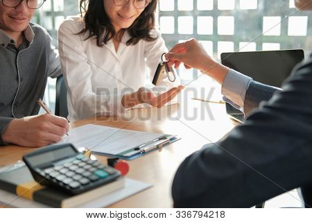 Dealer Salesman Giving Car Key To Owner. Client Signing Insurance Document Or Rental Car Lease Form