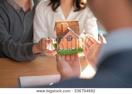 Lawyer Insurance Broker Giving House Model To Couple Customer. Realtor Selling Real Estate Property.