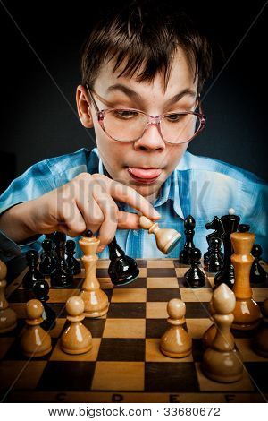 wunderkind play chess. Nerd boy.