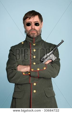 Man in the uniform of a military officer with a gun.