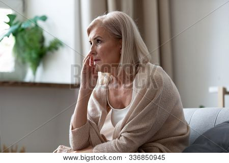 Pensive Middle-aged Woman Seated On Couch Lost In Thoughts