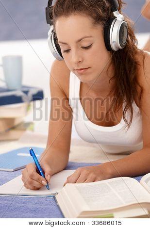 attraktive Mädchen lernen zu Hause mit Stock, mit Kopfhörer.
