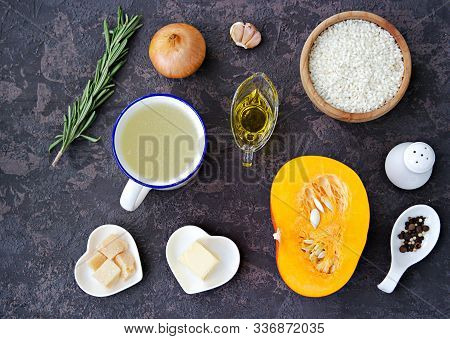Ingredients For Cooking Risotto With Pumpkin On A Dark Concrete Background: Dry Arborio Rice, Raw Pu