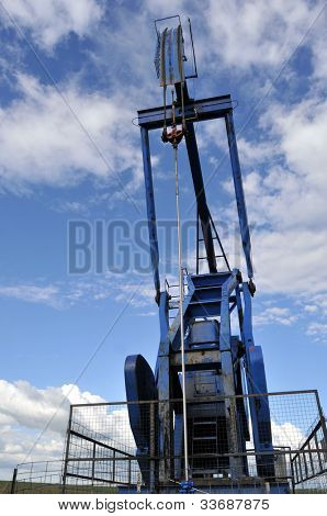Low-angle vertical closeup of a blue pump jack against the sky, head and rod (bridle) up close