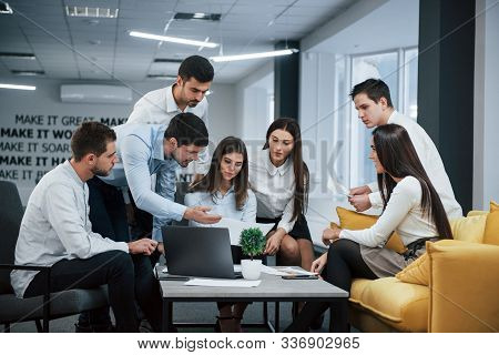 Guy Shows Document To A Girl. Group Of Young Freelancers In The Office Have Conversation And Working
