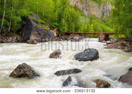 Wooden Bridge Of Logs On Mountain River. Crossing For Pedestrians Over Fast Creek