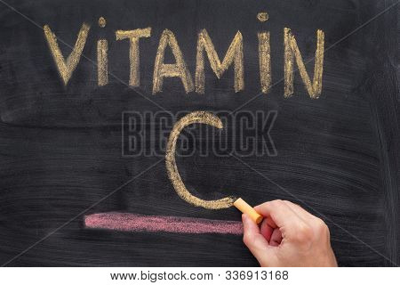 Man Writing Words Vitamin C On Chalkboard. Vitamin C Concept. Close Up.