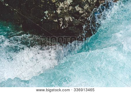 Mountain River With Stone In Blue Water. Turquoise Waves Of Sea Tide