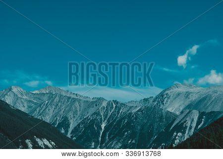 Snow Cliffs Under Blue Sky. Travel In  Mountains