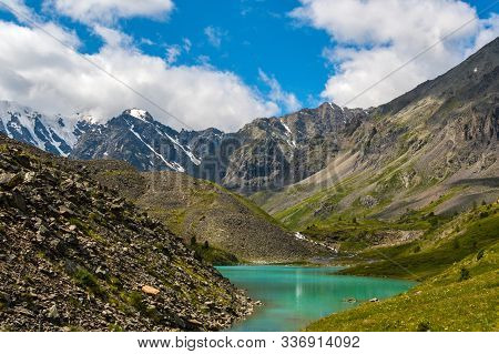 Mountain Blue Lake Among Rocks. Stone Ridge In River Valley Under Clouds. Travel In Mountains Among