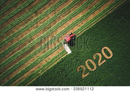 2020 Happy Ney Wear Concept And Red Tractor Mowing Green Field.