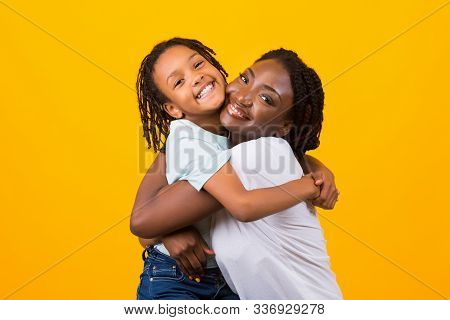 Children Adoption Concept. African American Mother Hugging Her Foster Child, Yellow Studio Backgroun