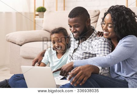 Joyful African American Family Of Three Using Laptop At Home Together, Watching Movie Or Browsing In