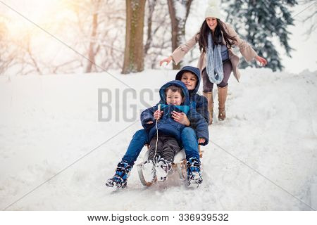 Young, Beautiful Mom And Her Cute Little Boy Enyoing Winter, Sledding