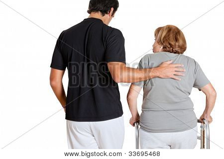 Rear view of trainer assisting senior woman with her walker over white background