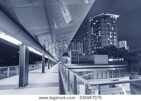 Modern Pedestrian Walkway In Midtown Of Hong Kong City At Night