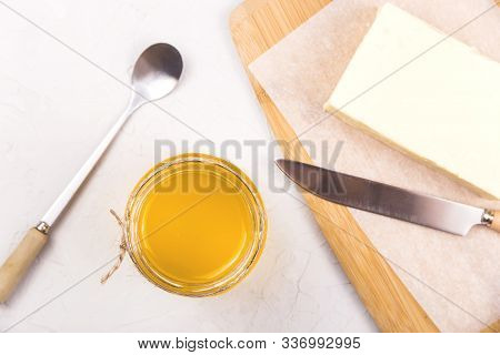 Ghee Or Clarified Butter In A Glass Jar On A Neutral Textured Background Next To A Spoon.