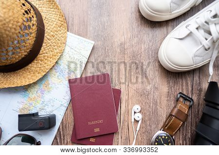Passport With A Map On Wooden Background.travel Planning.top View Of Traveler Accessories With A Hat