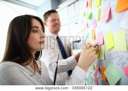 Portrait Of Beautiful Woman Sticking Colourful Notes On Board At Workplace. Co-workers Making Biz Re
