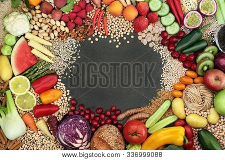 Vegan health food border with a large collection of foods. High in protein, vitamins, minerals, anthocyanins, antioxidants, fibre, omega 3 and smart carbs. Sustainable healthy food concept. Flat lay.