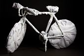 A bicycle covert in paper towels on black background poster