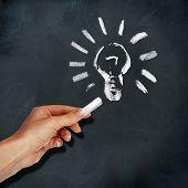 School blackboard and human hand drawing light bulb symbol poster