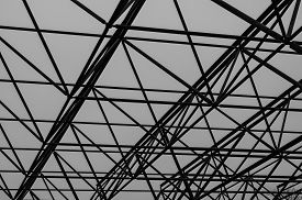Fragments Of The Roof Of A Standing Industrial Warehouse. Metal Sections And Trusses. View From The