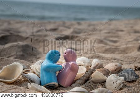 Ceramic Couple Dolls And Shells In Sand On The Beach And Copy Space. Concept For Anniversary, Weddin