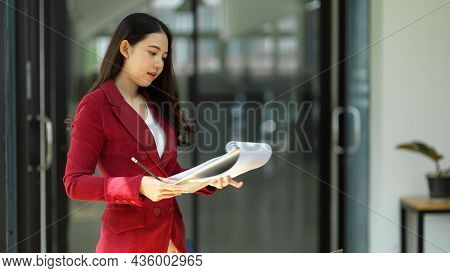 Young Millennial Asian Female Entrepreneur Reading Paperwork Documents.