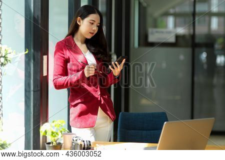 Successful Business Woman In The Office Looking On Smartphone.