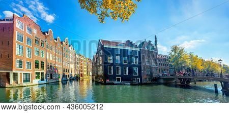 Panoramic view of the historic city center of Amsterdam. Traditional houses  of Amsterdam. Beautiful autumn sunny day and the serene reflection of houses in the water. Europe, Netherlands