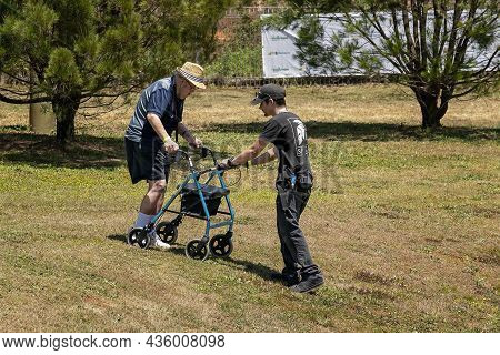 Eungella, Queensland, Australia - October 2021: A Young Man Assists And Elderly Male With Walking Fr