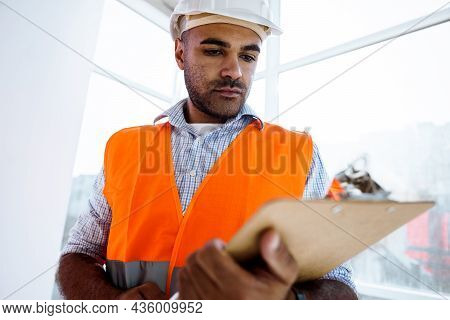 Foreman At Work On Construction Site Checking His Notes On Clipboard