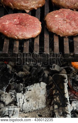 Raw Meatballs For Burgers Are Fried On Grill. Meat Is Roasting On Bbq Grill Over Hot Coals Outdoor.