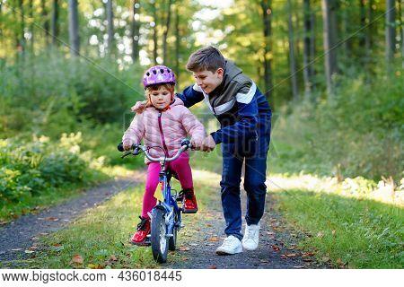 Cute Little Preschool Girl In Safety Helmet Riding Bicycle. School Kid Boy, Brother Teaching Happy H