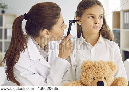 Otolaryngologist Examining Childs Ear With Otoscope During Checkup At Her Office