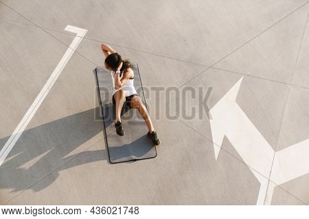 Black sportswoman doing exercise while working out on fitness mat on parking outdoors