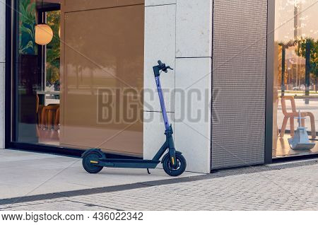 Electric Urban Transportation. Human Is Ready To Discover The Urban City In Autumn At Sunset With El
